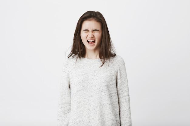 Portret van een kinderachtige tiener die op het punt staat te huilen, met gesloten ogen staat en hardop schreeuwt.