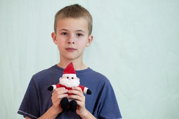 Portret van een kindjongen die met een klein stuk speelgoed van de kerstman speelt.