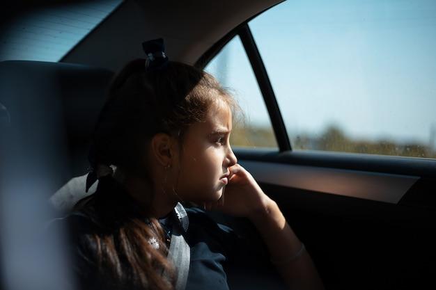 Portret van een kindmeisje dat in de auto zit en naar het raam kijkt.