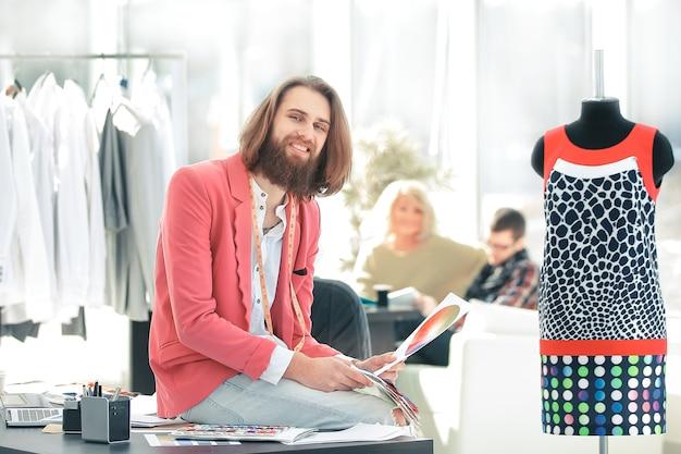 Portret van een kledingontwerper zittend op een bureau in de studio