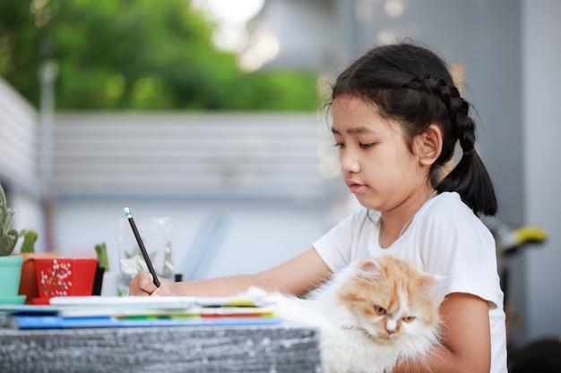 Portret van een klein aziatisch meisje dat huiswerk doet terwijl ze haar kat vasthoudt