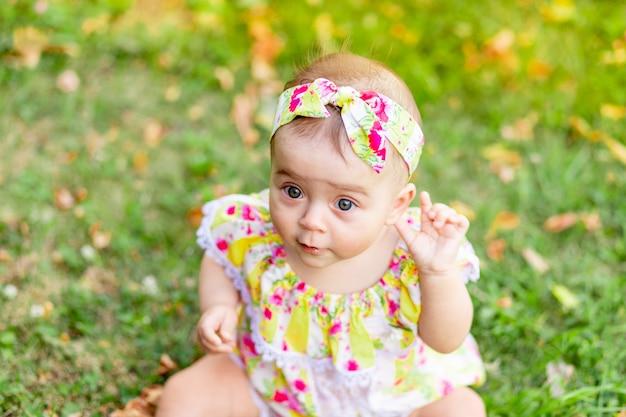 Portret van een klein babymeisje 7 maanden oud zittend op het groene gras in een gele jurk, wandelen in de frisse lucht
