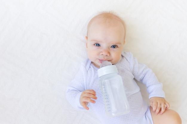 Portret van een klein babymeisje in een wit romper liggend op haar rug op een bed met een fles water