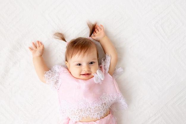 Portret van een klein babymeisje op een wit bed in roze kleren