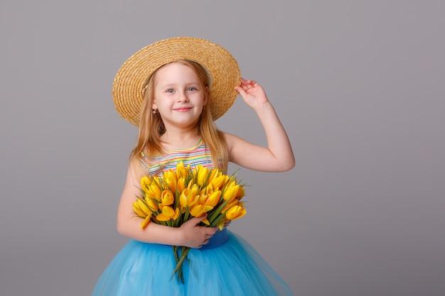 Portret van een klein blond meisje in een strooien hoed met een boeket van lentebloemen op een witte ruimte