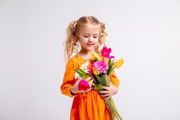 Portret van een klein blond meisje met een boeket van lentebloemen op een lichte muur