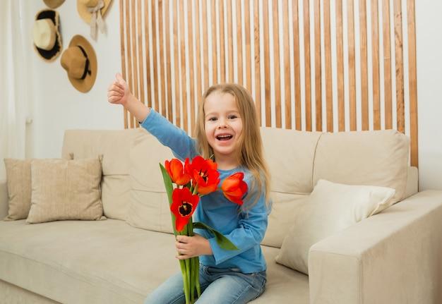 Portret van een klein blond meisje, zittend op een bank en rode tulpen te houden