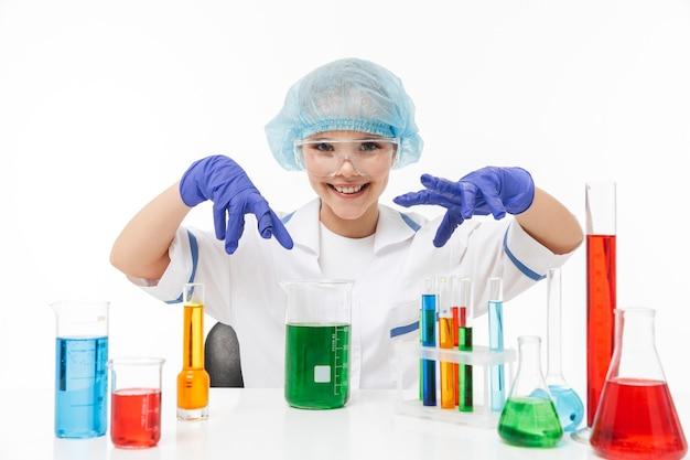 Portret van een klein chemicusmeisje in een witte laboratoriumjas die chemische experimenten maakt met veelkleurige vloeistof in reageerbuizen geïsoleerd over een witte muur