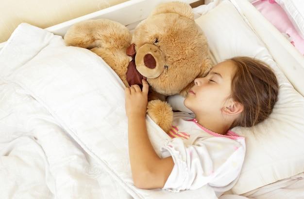 Portret van een klein donkerbruin meisje dat in bed slaapt met een teddybeer