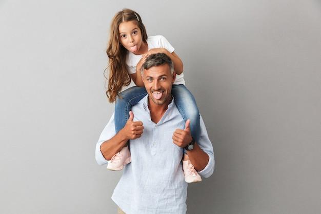Portret van een klein europees meisje met plezier en zittend op de nek van haar vader, geïsoleerd over grijs
