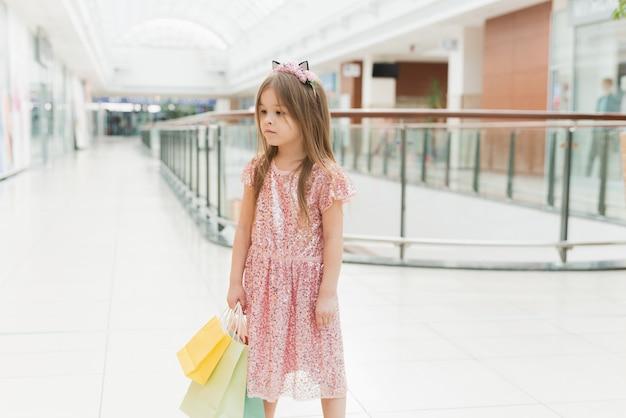 Portret van een klein gelukkig meisje in het winkelcentrum. een lachend lachend meisje in een roze jurk met een schattige rand met oren en met veelkleurige tassen in haar handen