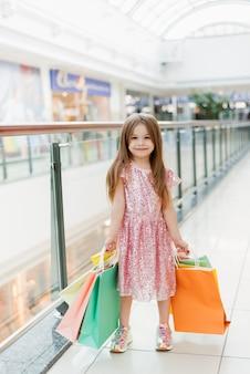Portret van een klein gelukkig meisje in het winkelcentrum. een lachend lachend meisje in een roze jurk met veelkleurige tassen in haar handen houdt zich bezig met winkelen. sjabloon voor uw advertentie
