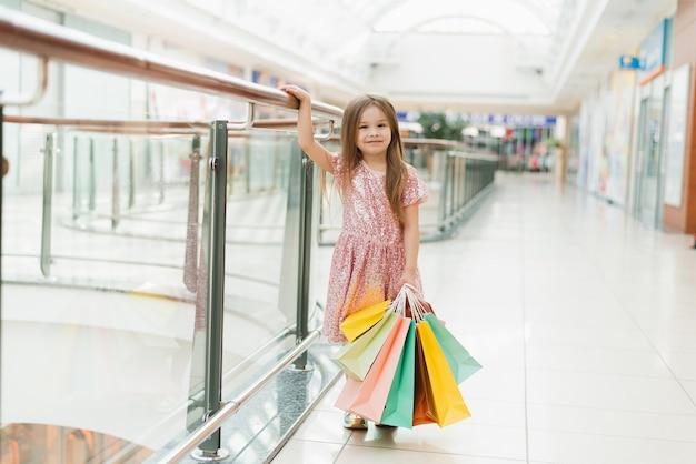 Portret van een klein gelukkig meisje in het winkelcentrum. een lachend lachend meisje in een roze jurk met veelkleurige tassen in haar handen houdt zich bezig met winkelen. sjabloon voor uw advertentie.