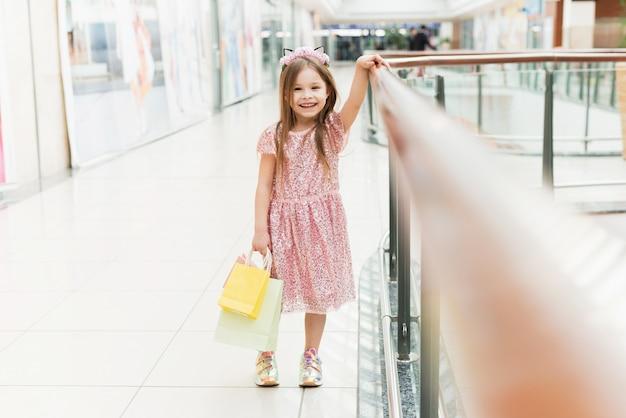 Portret van een klein gelukkig meisje in het winkelcentrum. een lachend lachend meisje in een roze jurk met veelkleurige tassen in haar handen houdt zich bezig met winkelen.
