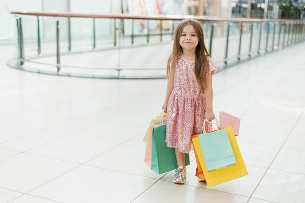 Portret van een klein gelukkig meisje in het winkelcentrum. een lachend lachend meisje in een roze jurk met veelkleurige tassen in haar handen loopt door het winkelcentrum en kijkt naar de etalages