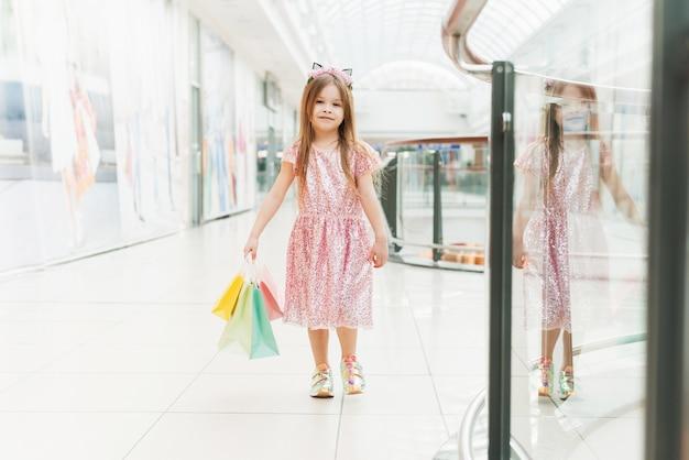 Portret van een klein gelukkig meisje in het winkelcentrum.