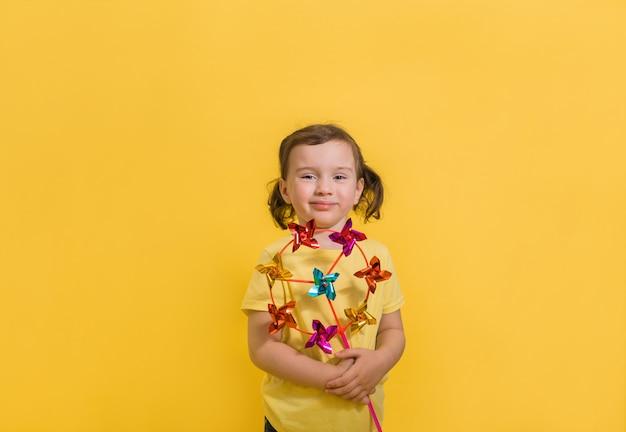 Portret van een klein glimlachend meisje dat een stuk speelgoed wind op geïsoleerd geel houdt