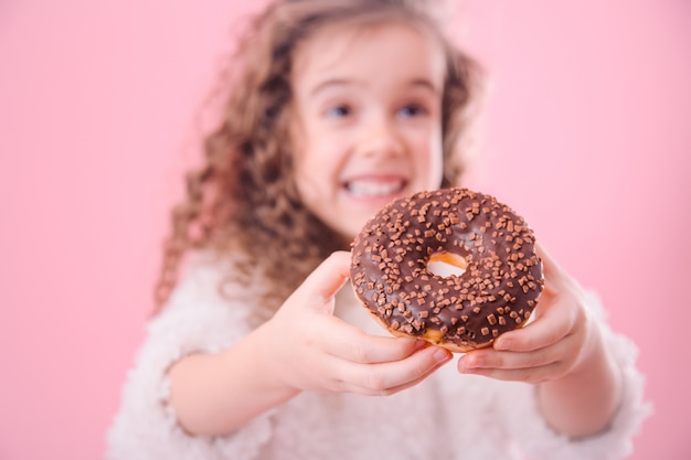Portret van een klein glimlachend meisje met donuts