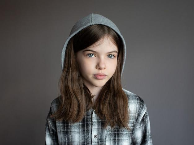 Portret van een klein jong mooi ernstig meisje in een hoodie op donker