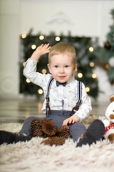 Portret van een klein jongensspel met denneappels dichtbij een kerstboom