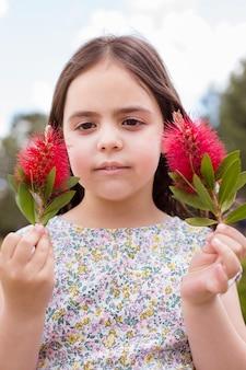 Portret van een klein kind buitenshuis. in elk van haar handen houdt ze een bloem.