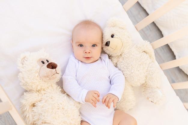 Portret van een klein kind een meisje van 6 maanden oud in een witte romper liggend op haar rug in een kinderbed met zacht speelgoed draagt
