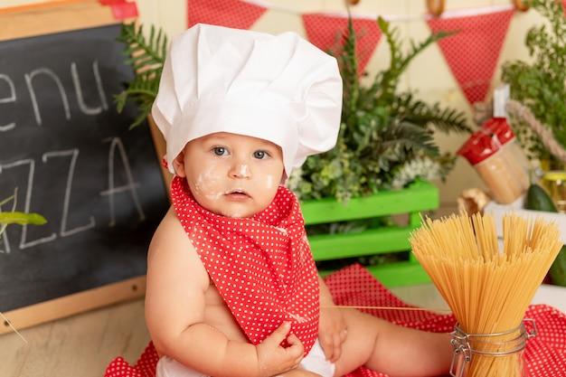Portret van een klein kind in een koksmuts die spaghetti in de keuken voorbereidt