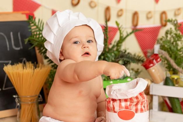 Portret van een klein kind in een koksmuts in de keuken met bloem