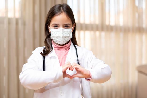 Portret van een klein kind verkleed als arts en een medisch masker dat een hart met haar handen vormt