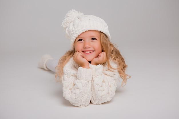 Portret van een klein krullend-haired meisje in een gebreide witte de winterhoed