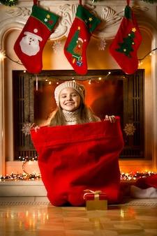 Portret van een klein lachend meisje dat in een rode tas zit voor geschenken bij de open haard