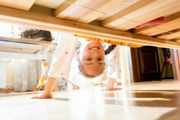Portret van een klein lachend meisje dat onder bed kijkt