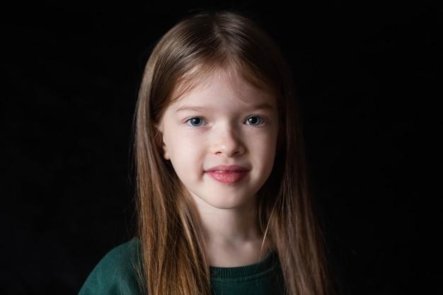 Portret van een klein lachend meisje met lang blond haar op zwart