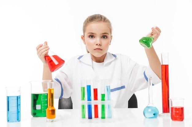 Portret van een klein leerling-meisje in een witte laboratoriumjas die chemische experimenten maakt met veelkleurige vloeistof in reageerbuizen geïsoleerd over een witte muur