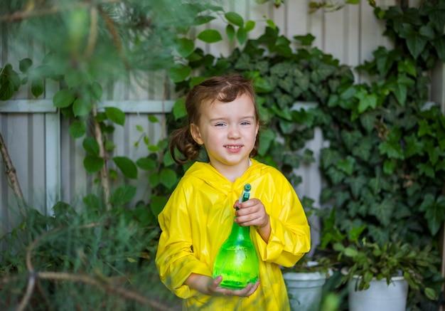 Portret van een klein meisje assistent in een gele regenjas en politisering in de kas voor planten en coniferen