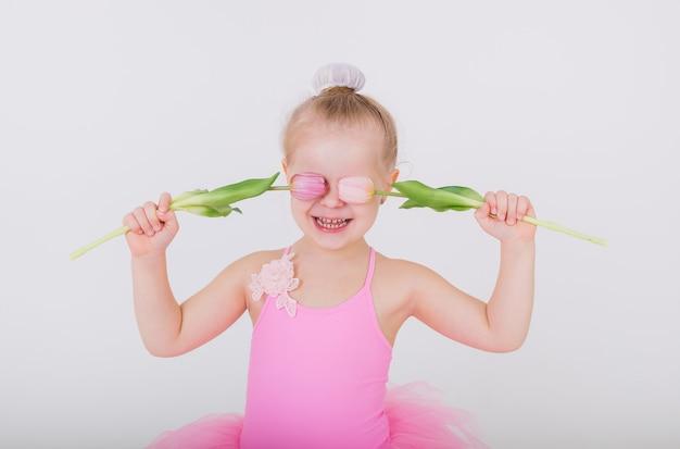 Portret van een klein meisje bedekte haar ogen met tulpen op een witte muur