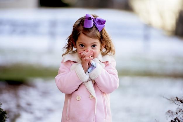 Portret van een klein meisje bidden in een park in de sneeuw onder het zonlicht