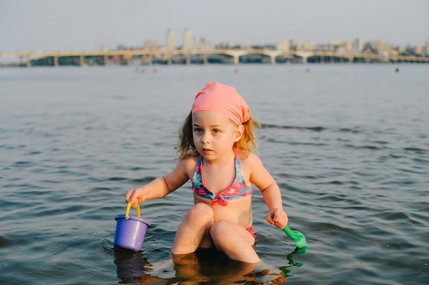 Portret van een klein meisje buiten in de zomer. klein meisje in een zwembroek in de zomer bij de rivier. zomer kindertijd
