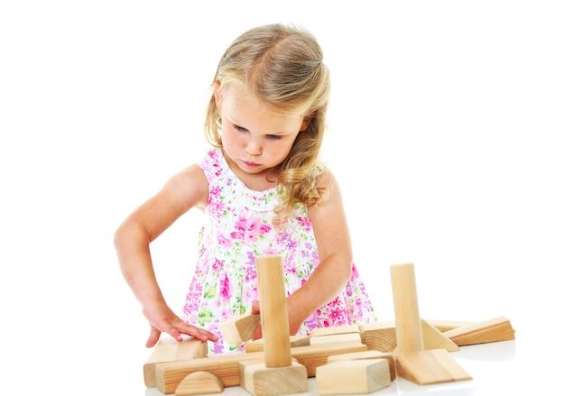 Portret van een klein meisje dat constructies bouwt met houten blokken op een witte achtergrond