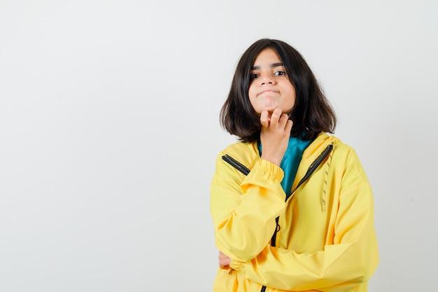 Portret van een klein meisje dat de hand onder de kin vasthoudt in hemd, jas en er mooi vooraanzicht uitziet