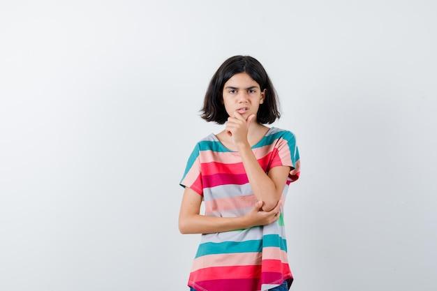 Portret van een klein meisje dat de hand op de kin in een t-shirt houdt en van voren overstuur kijkt