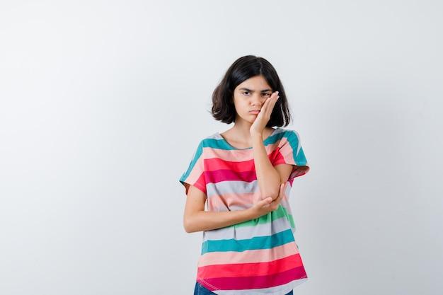 Portret van een klein meisje dat de hand op de wang in een t-shirt houdt en van voren overstuur kijkt