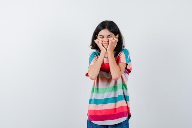 Portret van een klein meisje dat de handen op de wangen houdt in een t-shirt en er beledigd uitziet