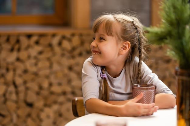 Portret van een klein meisje dat drinkt in een huiselijke omgeving