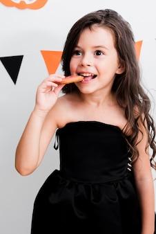 Portret van een klein meisje dat een koekje eet