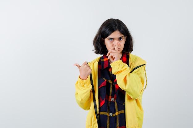 Portret van een klein meisje dat een stiltegebaar toont in een geruit overhemd, een jasje en een zelfverzekerd vooraanzicht