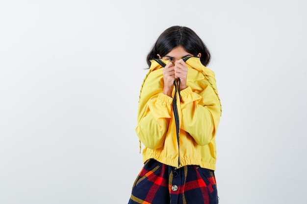 Portret van een klein meisje dat gezicht bedekt met jasje in geruit overhemd, jasje en schattig vooraanzicht kijkt