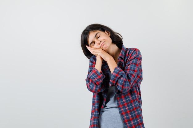 Portret van een klein meisje dat haar gezicht op haar handen in een geruit hemd dempt en er slaperig uitziet