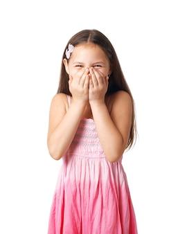 Portret van een klein meisje dat haar glimlach in haar handen verbergt.