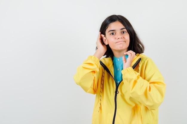 Portret van een klein meisje dat haar haar achter het oor in een shirt, jas stopt en zelfverzekerd vooraanzicht kijkt